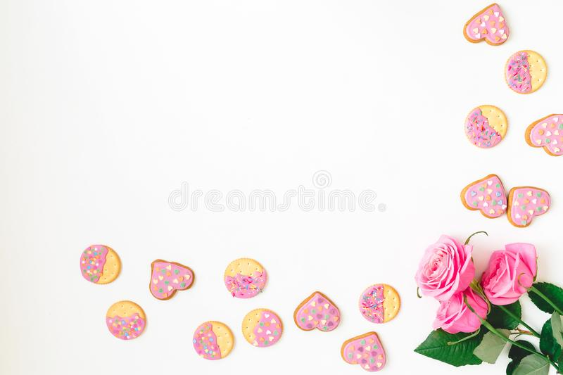 Gingerbread cookie with pink glaze and roses flower on white background. Flat lay. Top view. Woman day background royalty free stock photo