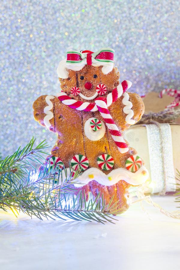 Gingerbread cookie and small gift box on bright festive Christmas background stock photo