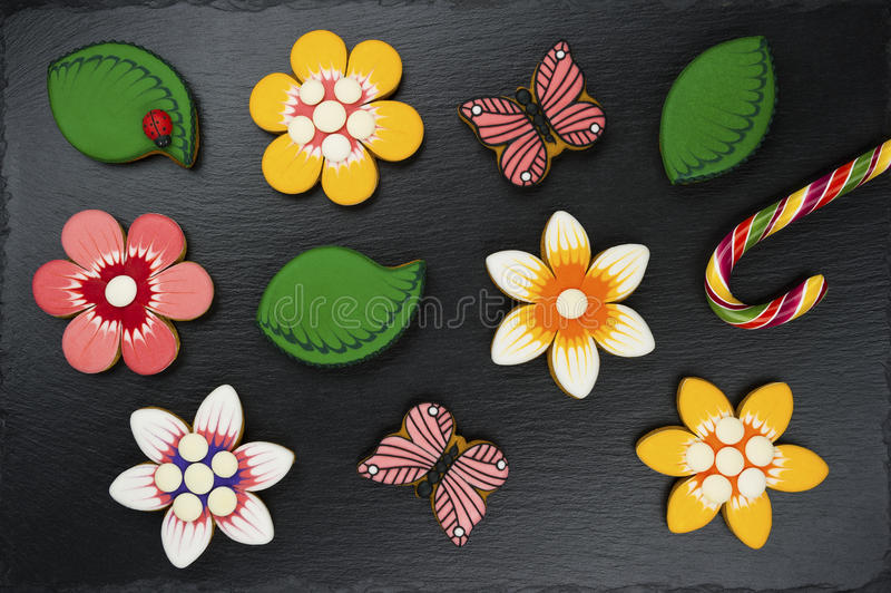 Gingerbread cookies with candy. Gingerbread cookies and candy on black background, colorful homemade cakes in shape of flower, leaf, butterfly on textured slate royalty free stock photos