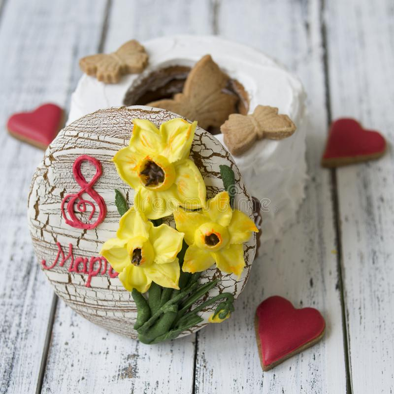 Gingerbread cookies casket with decor on 8 March holiday - yellow daffodils, red hearts cookies, butterflies, the inscription in royalty free stock image