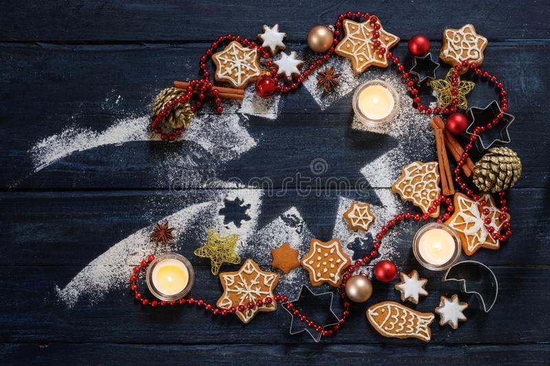 Gingerbread cookies, Christmas baubles, decoration and burning candles on a falling star shape from icing sugar on a dark blue stock photography