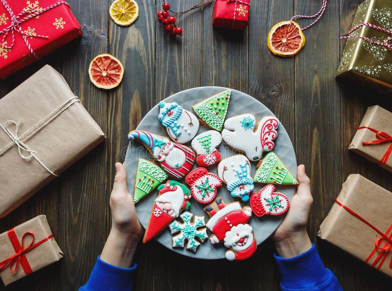 Gingerbread cookies for christmas, new year in kids hands on the wooden table. Festive, sweet pastry, delicious biscuits. Home celebration, decoration concept stock image