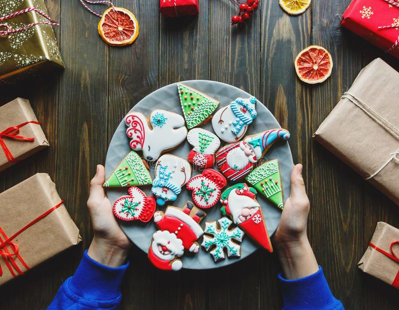 Gingerbread cookies for christmas, new year in kids hands on the wooden table. Festive, sweet pastry, delicious biscuits. Home celebration, decoration concept royalty free stock images