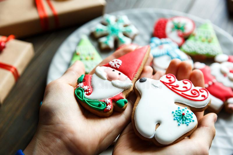 Gingerbread cookies for christmas, new year in kids hands on the wooden table. Festive, sweet pastry, delicious biscuits. Home celebration, decoration concept royalty free stock photos