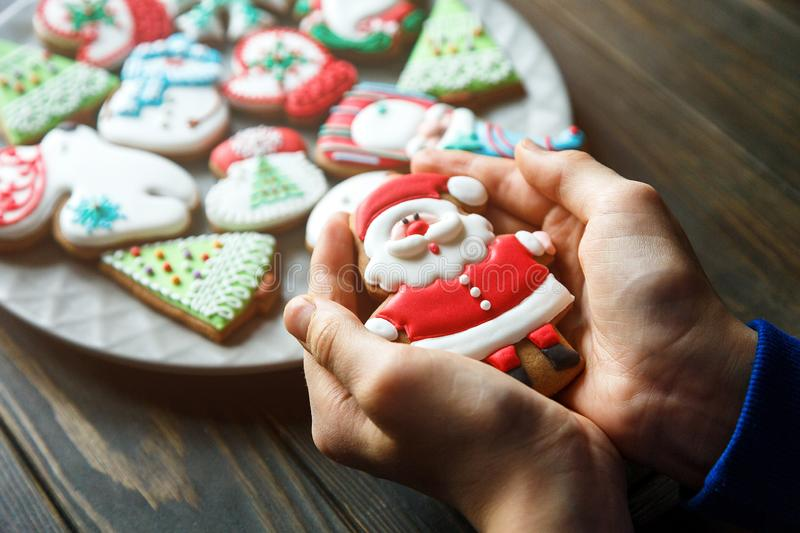 Gingerbread cookies for christmas, new year in kids hands on the wooden table. Festive, sweet pastry, delicious biscuits. Home celebration, decoration concept stock photo