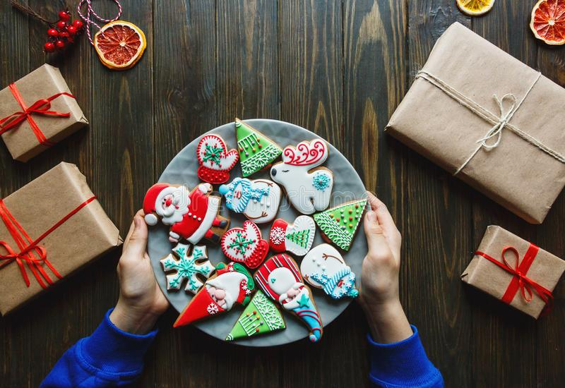 Gingerbread cookies for christmas, new year in kids hands on the wooden table. Festive, sweet pastry. Delicious biscuits royalty free stock images