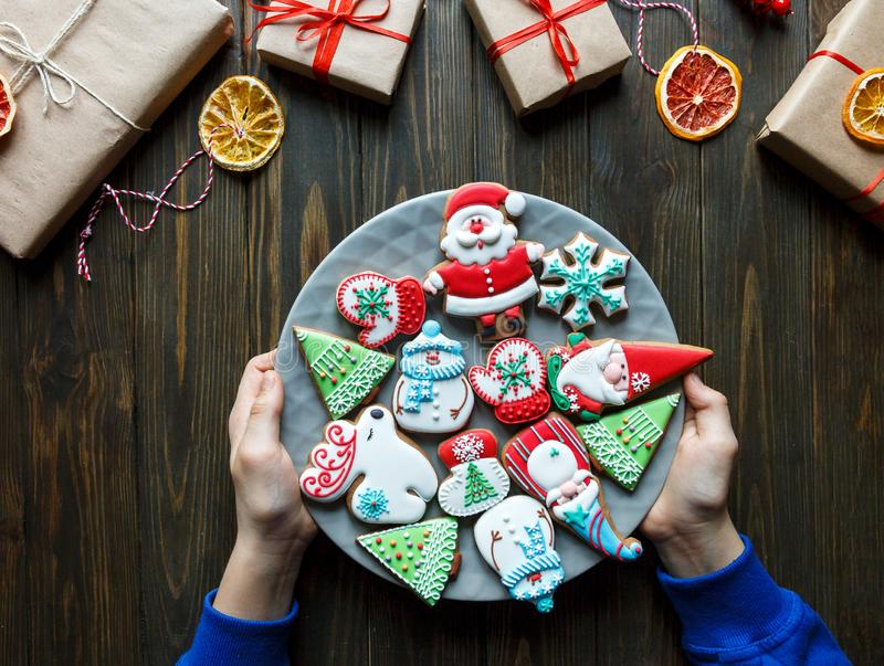 Gingerbread cookies for christmas, new year in kids hands on the wooden table. Festive, sweet pastry,. Delicious biscuits stock photos