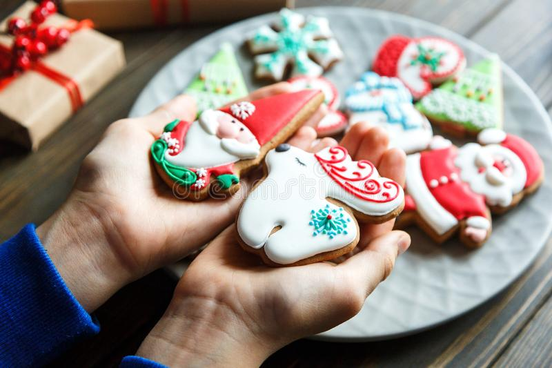 Gingerbread cookies for christmas, new year in kids hands on the wooden table. Festive, sweet pastry,. Delicious biscuits stock images
