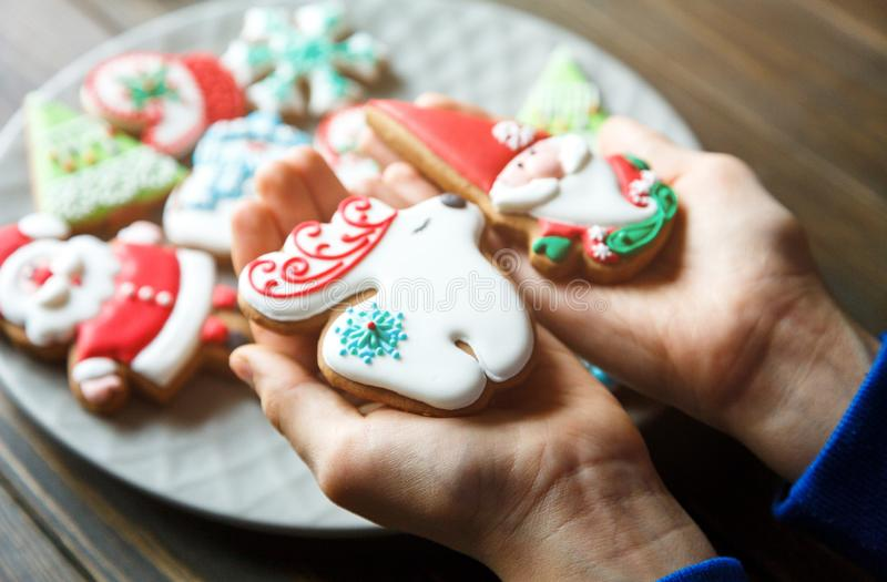 Gingerbread cookies for christmas, new year in kids hands on the wooden table. Festive, sweet pastry,. Delicious biscuits royalty free stock image