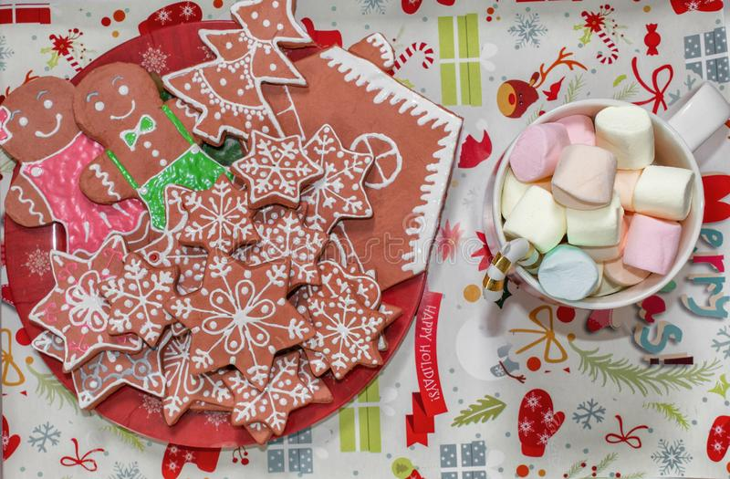 Gingerbread cookies, in the form of a gingerbread man, stars on a tray and a cup of marshmallow, Christmas treats. Christmas tree. Decorations and gifts stock photo