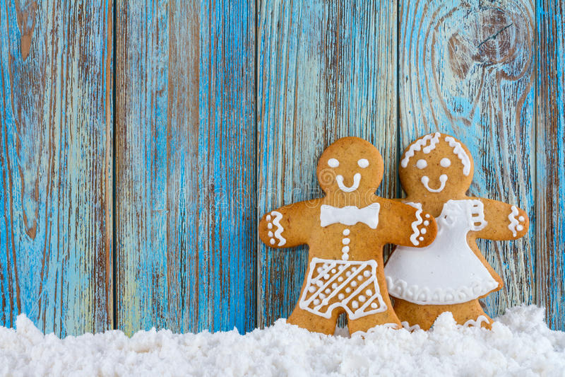 Gingerbread cookies, gingerbread men in the snow on blue wooden background, template greeting card royalty free stock photos