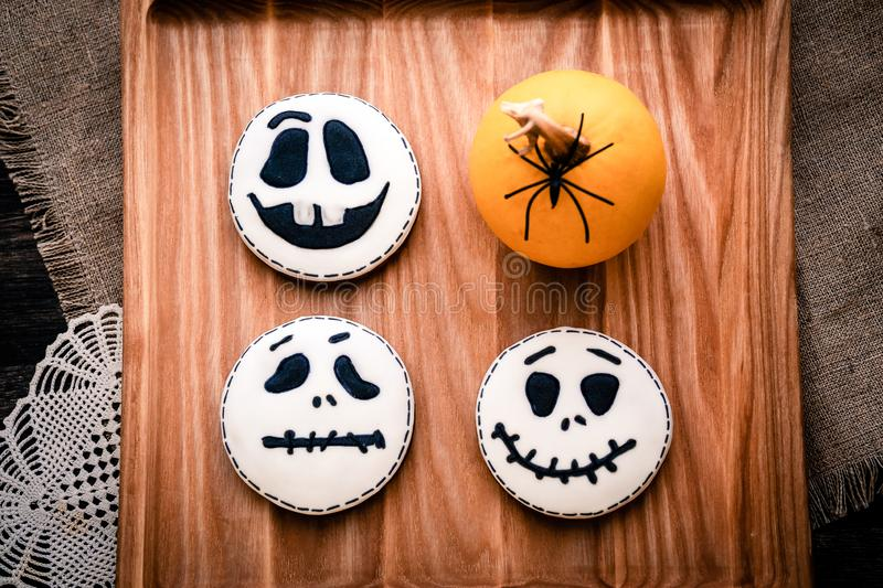 Gingerbread cookies for Halloween party. Head White ghost with eyes and small yellow decorative pumpkin with black spider. On a light wooden surface with pink stock photo