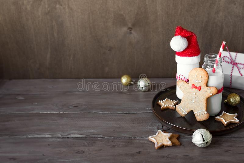 Gingerbread cookies and milk. Christmas composition with Gingerbread cookies and milk on wooden background, copy space. Cookies and milk for Santa stock photos
