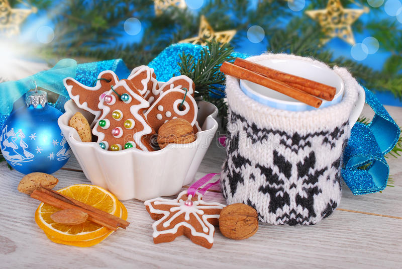 Gingerbread cookies and milk in cup with knitted cover for santa. Christmas gingerbread cookies and milk in cup with knitted cover waiting for santa claus royalty free stock photography