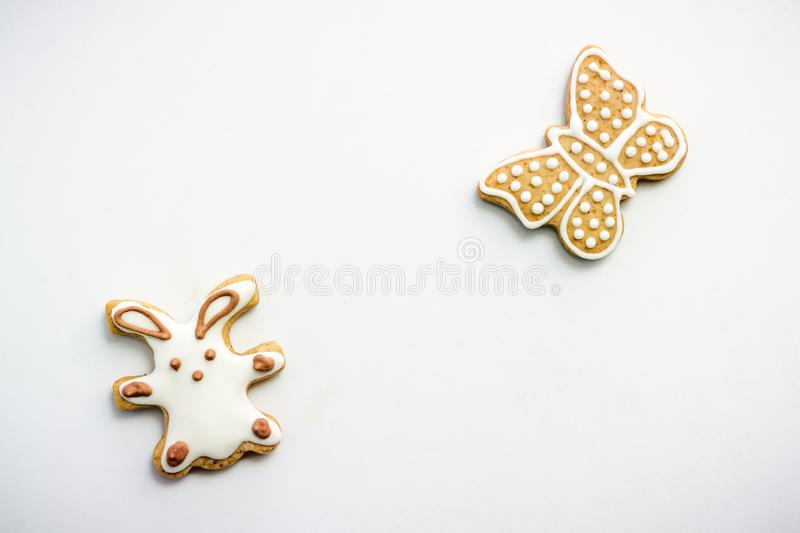 Gingerbread cookies in the shape of Easter bunny and butterflies, covered with white and chocolate icing-sugar. On white table stock photos