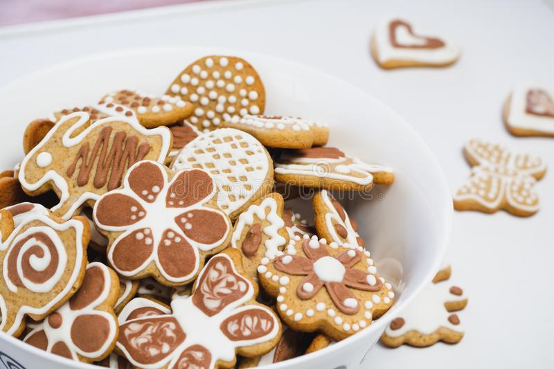 Gingerbread cookies in the shape of an Easter bunny, butterflies and flowers, covered with white and chocolate icing-sugar. In a white dish on a white surface royalty free stock images