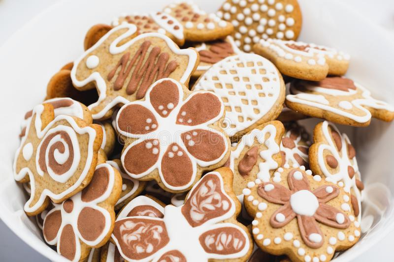 Gingerbread cookies in the shape of an Easter bunny, butterflies and flowers, covered with white and chocolate icing-sugar. In a white plate royalty free stock photo