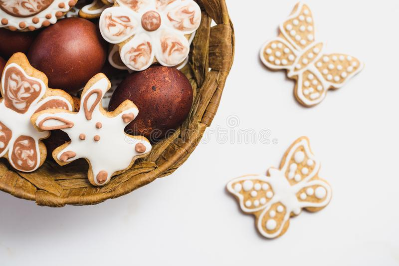 Gingerbread cookies in the shape of an Easter bunny, flowers and butterflies, covered with white and chocolate icing-sugar, and Ea. Ster eggs in a brown wicker royalty free stock images