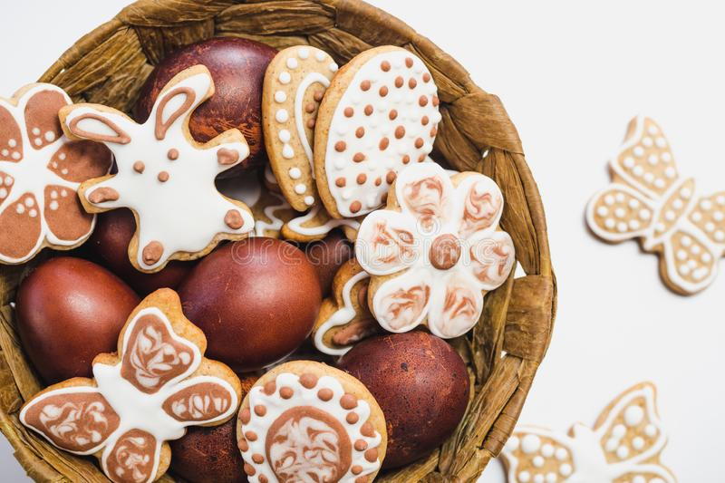 Gingerbread cookies in the shape of an Easter bunny, flowers, butterflies and hearts, covered with white and chocolate icing-sugar. And Easter eggs in a brown royalty free stock photo