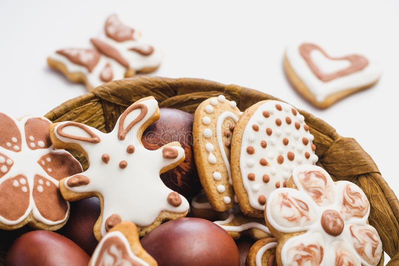 Gingerbread cookies in the shape of an Easter bunny, flowers, butterflies and hearts, covered with white and chocolate icing-sugar. And Easter eggs in a brown royalty free stock images