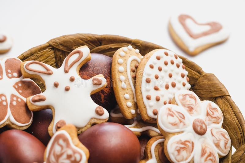 Gingerbread cookies in the shape of an Easter bunny, flowers and hearts, covered with white and chocolate icing-sugar, and easter. Chicken eggs in a brown royalty free stock photos