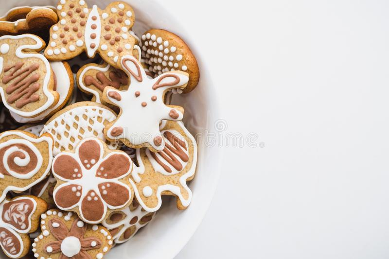 Gingerbread cookies in the shape of Easter bunny, heart, butterfly and flowers, covered with white and chocolate icing. Sugar, in a white dish on a white stock photography