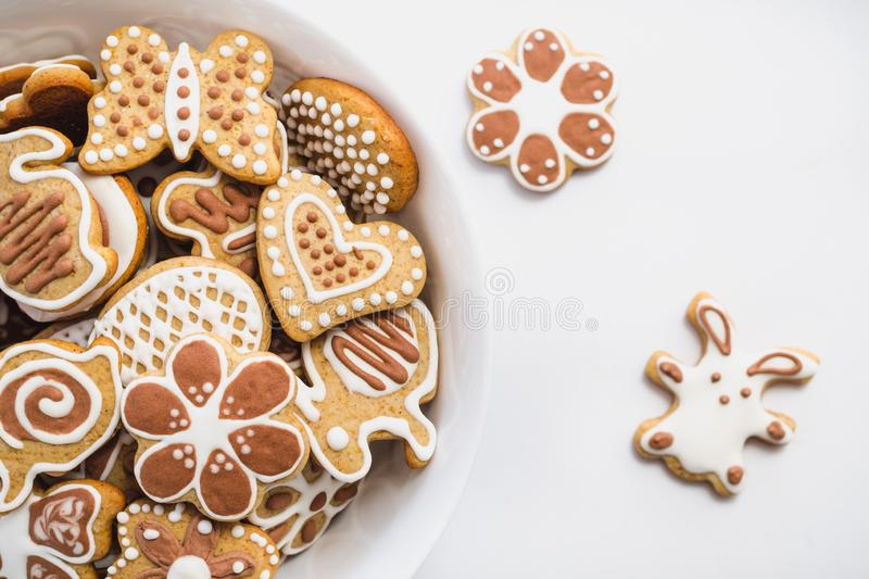 Gingerbread cookies in the shape of Easter bunny, heart, butterfly and flowers, covered with white and chocolate icing-sugar. In a white dish on a white royalty free stock images