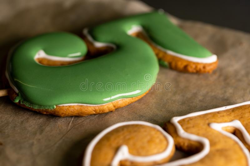 Gingerbread cookies on a shelf with green icing in the form of numbers five royalty free stock images
