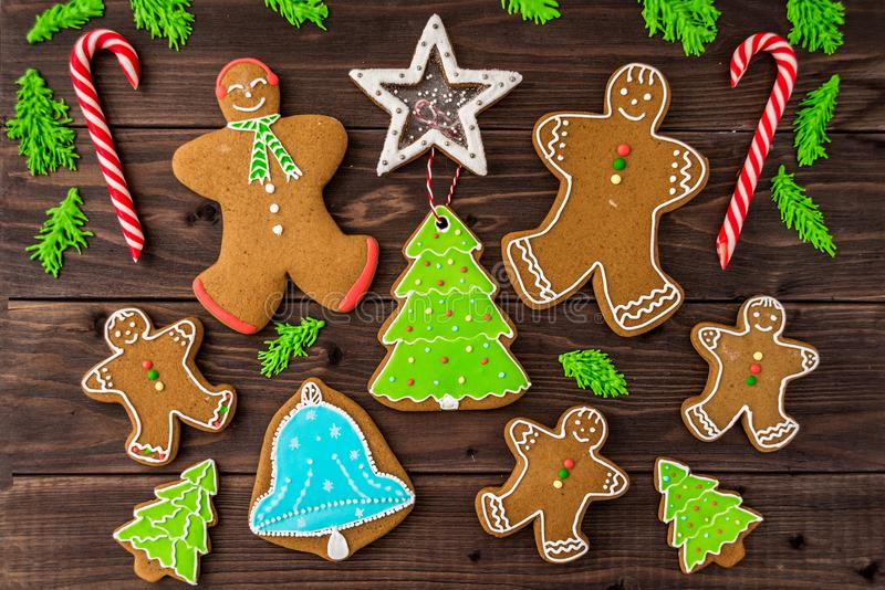 Gingerbread cookies, snowflakes, Christmas tree, bell, man, hanging with ribbon over a dark brown wood background. Free. Gingerbread cookies, snowflakes stock photos