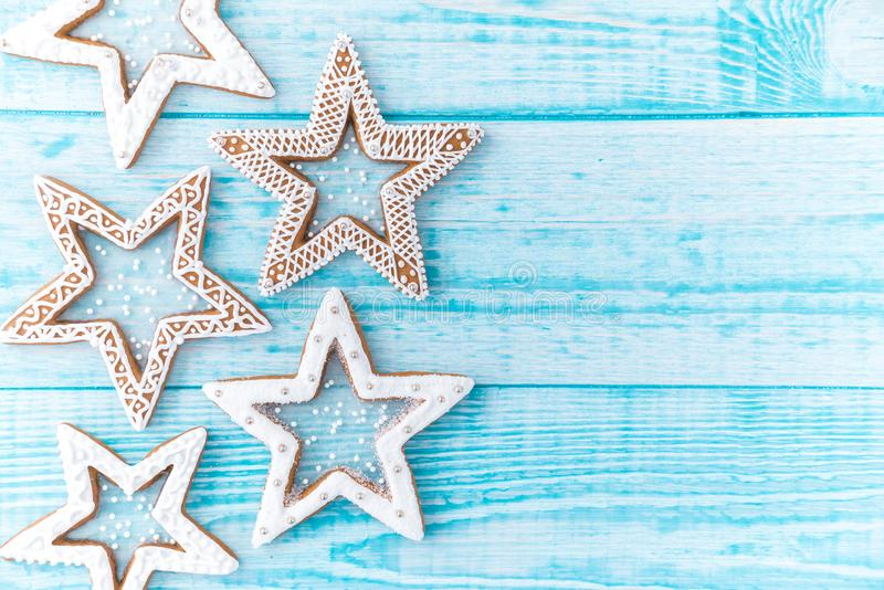 Gingerbread cookies, snowflakes hanging with ribbon over a blue wood background. Free space copyspace for your text. stock image