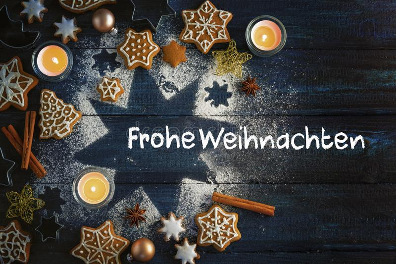 Gingerbread cookies, spices and burning candles on a star from icing sugar on a dark blue wooden background, German text Frohe royalty free stock photography