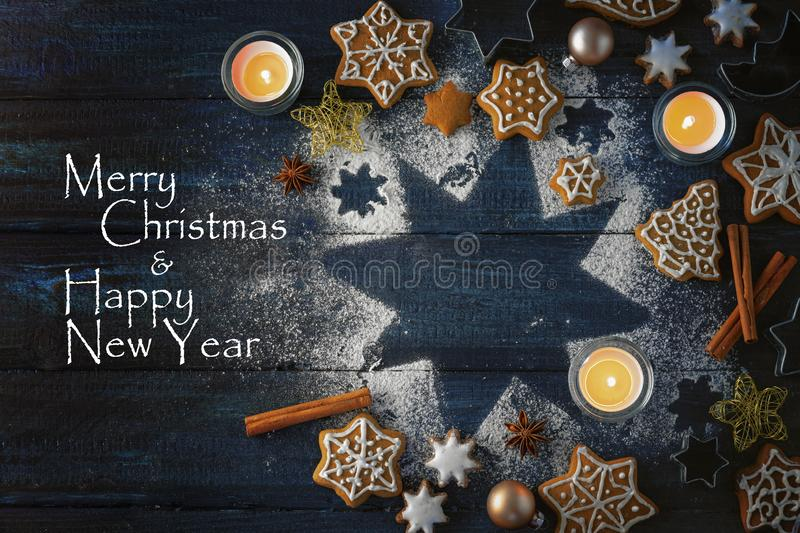 Gingerbread cookies, spices and burning candles on a star from icing sugar on a dark blue wooden background, text Merry Christmas. And Happy new Year, high stock image