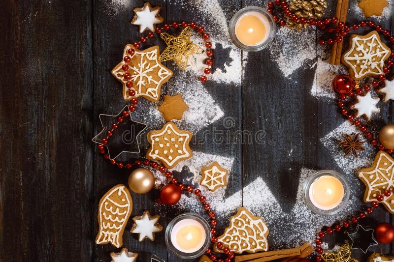 Gingerbread cookies, spices and burning candles on a star shape from icing sugar on a dark rustic wooden background, Christmas. Composition with copy space stock images