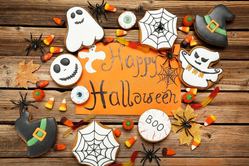 Gingerbread cookies with text Happy Halloween. On brown wooden table stock image