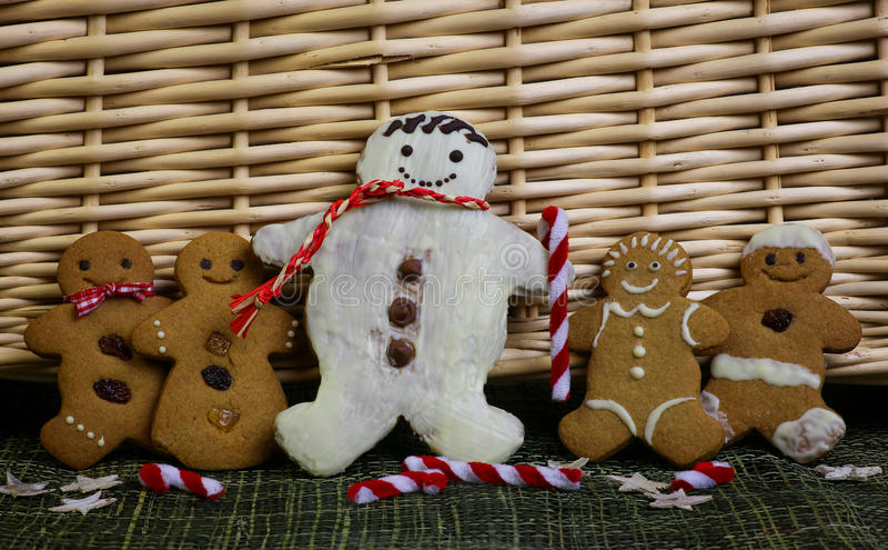 Gingerbread family snowman. With gingham ribbons, green ribbon and christmas decoration, wicker basket in background royalty free stock photos