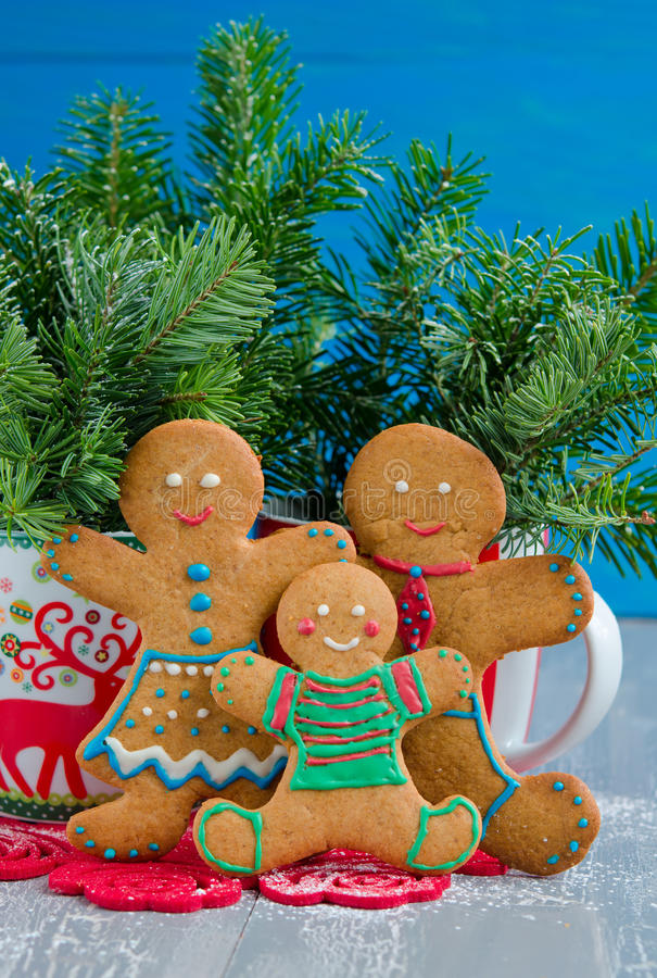 Gingerbread family. On the white wooden background stock photography