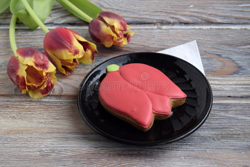 Gingerbread in the form of tulip is on a plate. Tulips are on a wooden table royalty free stock photo