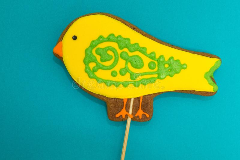 Gingerbread in the form of a yellow `bird` on a blue background. Gingerbread in the form of a yellow `bird` on a blue background stock photos