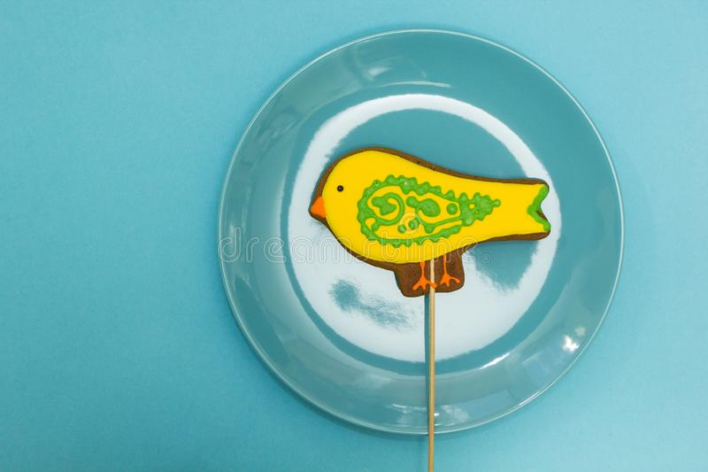 Gingerbread in the form of a yellow `bird` in a blue plate on a blue background. Gingerbread in the form of a yellow `bird` in a blue plate on a blue background royalty free stock photography