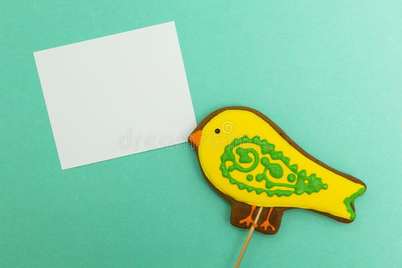Gingerbread in the form of a yellow `bird` with a white leaf on a green background, space for text.  royalty free stock photo