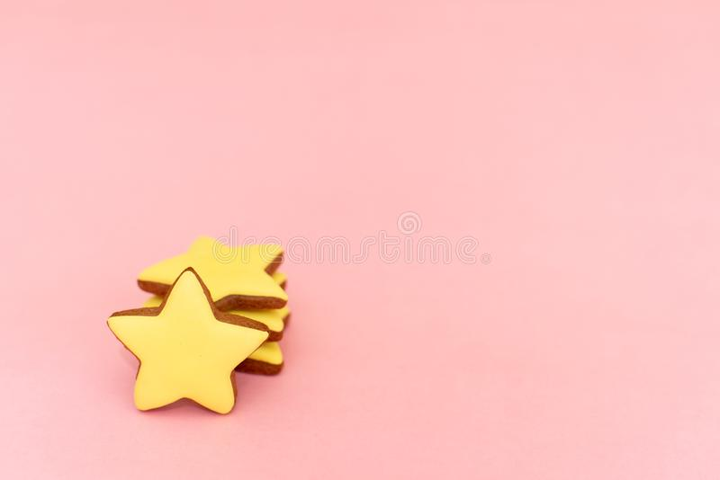 Gingerbread in the form of yellow stars on a pink background.  royalty free stock image