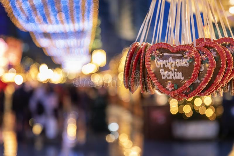 Gingerbread heart cookies on a Christmas market in Germany writing `Greetings from Berlin`. With christmas lights and bokeh stock photos