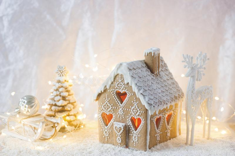 Gingerbread house, Christmas trees and a figure of a deer on a luminous background. Bokeh effect. Gingerbread house, Christmas trees and a figure of a deer on a royalty free stock photos
