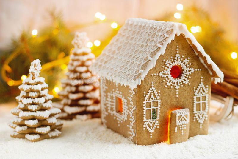 Gingerbread house and Christmas trees on a luminous background. Bokeh effect. royalty free stock photo