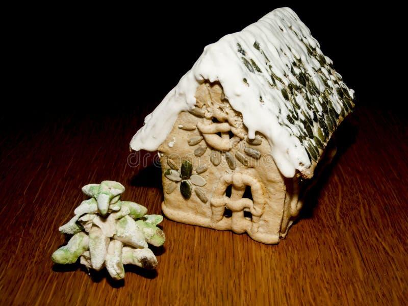 Gingerbread House en een dennenboom op de houten tafel stock fotografie