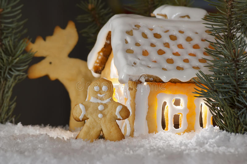 Gingerbread house, man and elk. Gingerbread house with gingerbread man, elk and christmas trees. Gingerbread man cookie behind the door. Christmas decoration stock photography