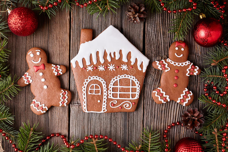 Gingerbread house, man and woman cookies christmas. Composition in new year decorations frame on vintage wooden table background. Top view. Homemade traditional royalty free stock photo