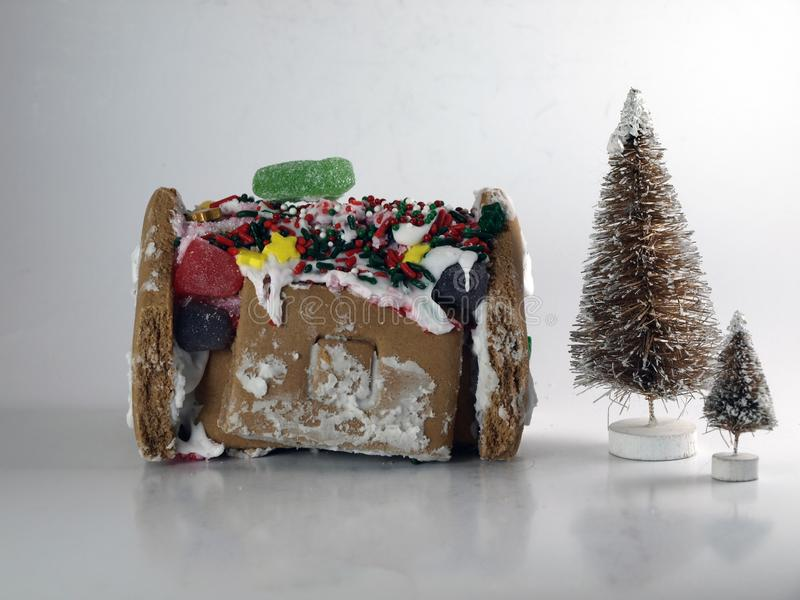 Gingerbread House Poorly Constructed Beside Two Artificial Christmas Trees royalty free stock photo