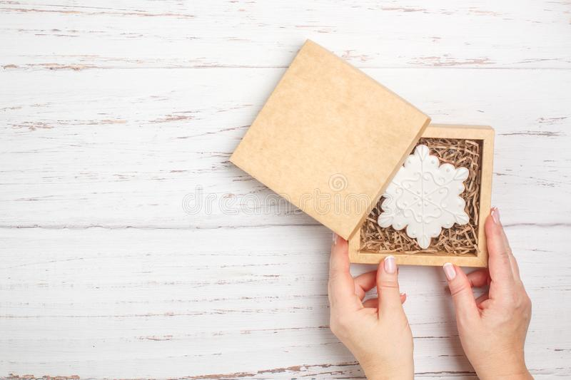 Gingerbread in icing sugar in the form of snowflakes. Traditional New year and Christmas gift. The concept of the celebration.  Woman packs cookies in craft stock image