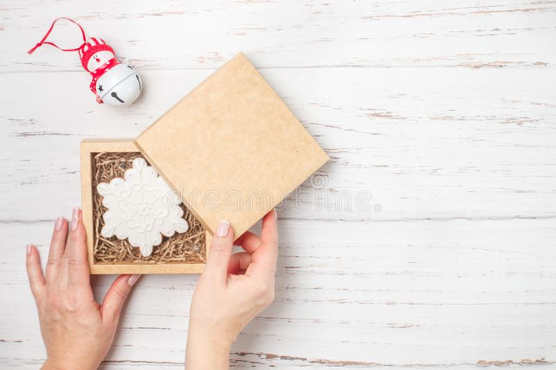 Gingerbread in icing sugar in the form of snowflakes. Traditional New year and Christmas gift. The concept of the celebration.  Woman packs cookies in craft stock photography